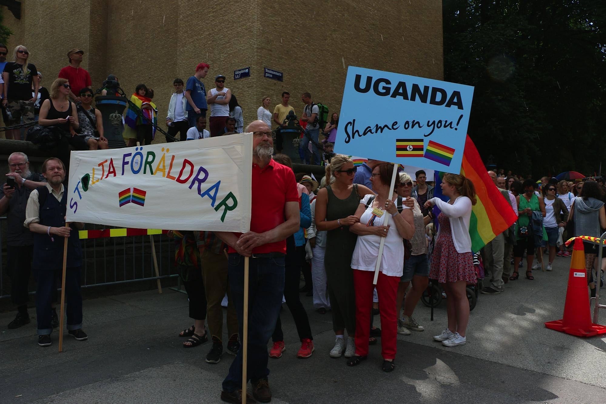 stolta föräldrar i parad med stor färgglad banderoll som det står stolta föräldara på