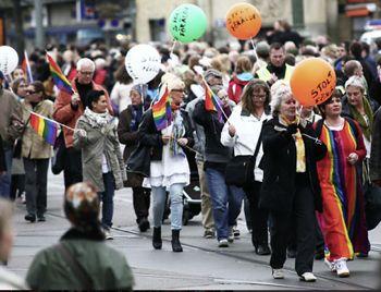 bild från prideparad med glada människor som bär ballonger och regnbågsflaggor.